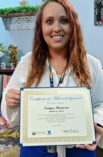 photo of Tanya Brunson holding a certificate she was awarded from Vocational Rehabilitation